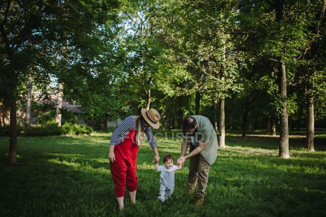 Мать и отец держатся за руки со своим сыном — стоковое фото