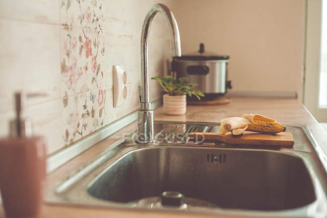 Banana on a chopping board by the kitchen sink — Stock Photo