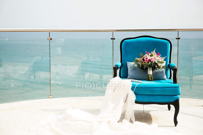 Wedding dress and Bridal bouquet on an armchair — Stock Photo