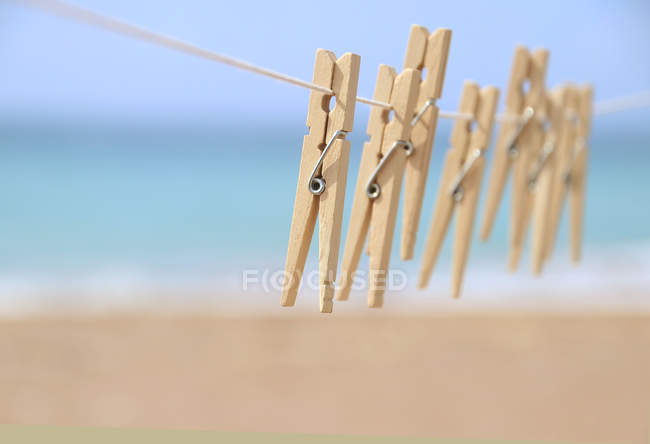 Clothes pegs on a washing line by the beach — Stock Photo
