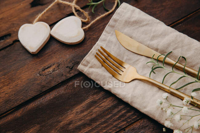 Gold cutlery and heart shape decorations — Stock Photo