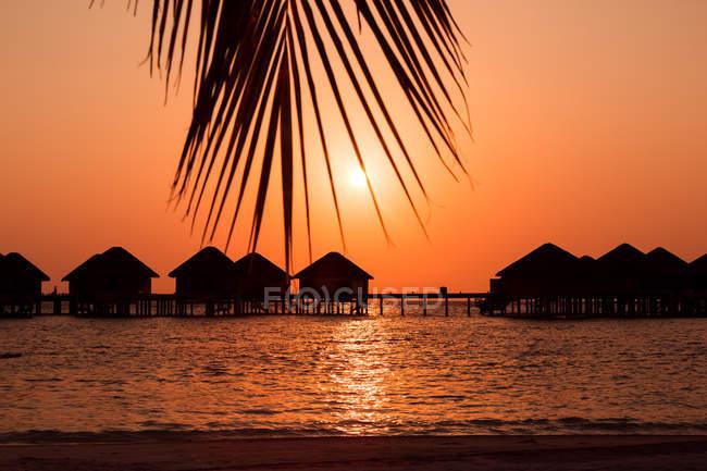 Silhouette de bungalows en bois dans l'eau de mer, Maldives — Photo de stock