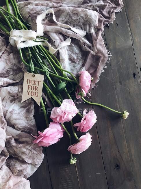 Blumenstrauß aus Ranunkeln mit Schal und Geschenkanhänger — Stockfoto