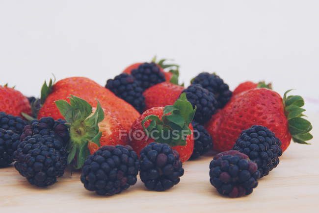 Closeup view of Strawberries and blackberries on a chopping board — Stock Photo