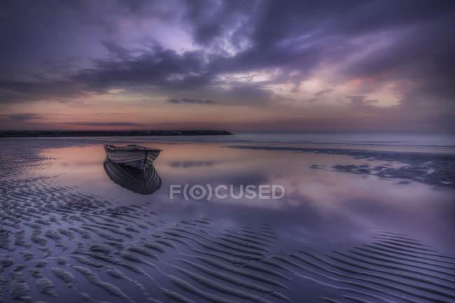 Barco en una playa en marea baja, Jesolo, Veneto, Italia - foto de stock