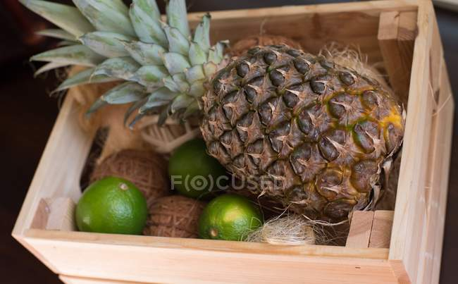 Closeup view of Pineapple and limes in a wooden crate — Stock Photo