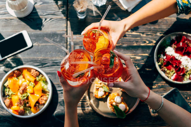 Overhead view of three women making a celebratory toast with aperol spritz cocktails — Stock Photo