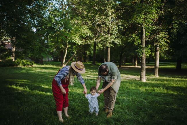 Madre y padre tomados de la mano con su hijo - foto de stock