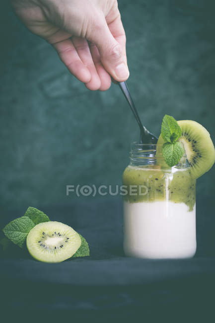 Woman eating a kiwi yogurt, closeup view — стокове фото