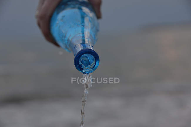 Human hand pouring a bottle of water — Stock Photo