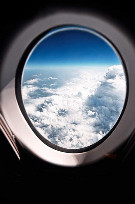 Scenic view through an airplane window on clouds — Stock Photo