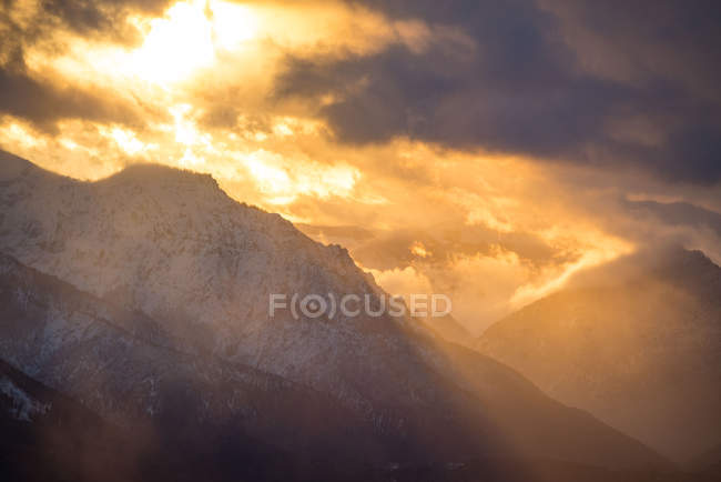 Sun breaking through the clouds between snow covered mountains, Untersberg, Salzburg, Austria — Stockfoto