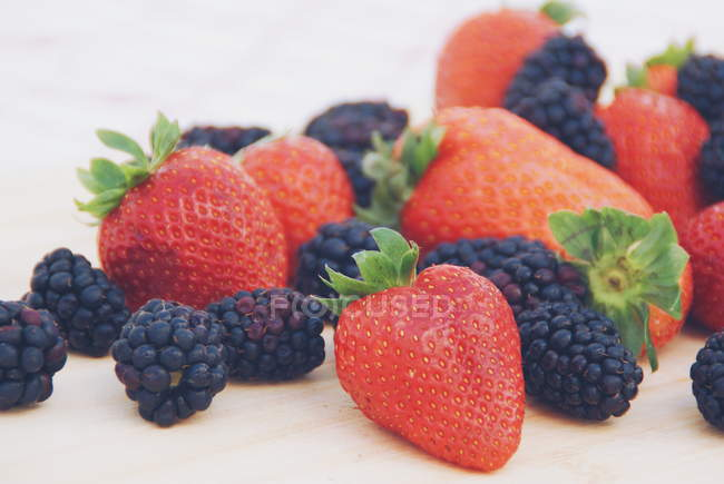Strawberries and blackberries on a chopping board — Stock Photo