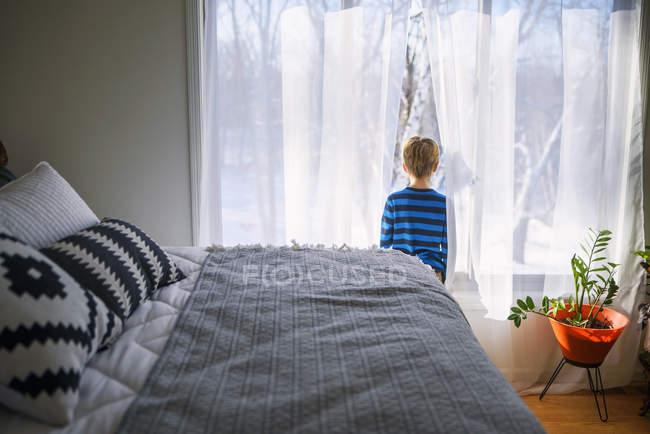 Мальчик, стоящий в спальне и смотрящий в окно на снег — стоковое фото