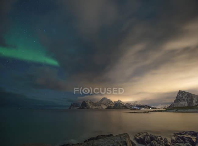 Vista panorámica de las luces boreales sobre las montañas, Myrland, Flakstad, Lofoten, Noruega - foto de stock