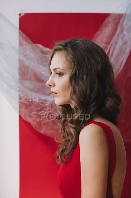 Retrato de una mujer de pie junto a una pared roja - foto de stock