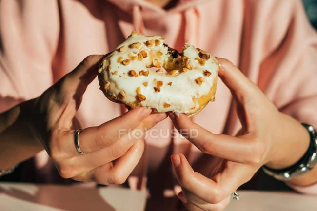 Женщина ест пончик, вид сверху вверх — стоковое фото
