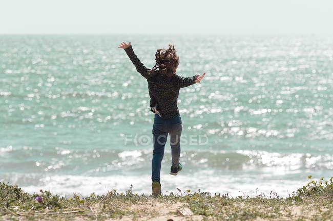 Fille sur la plage sautant dans les airs, Espagne — Photo de stock