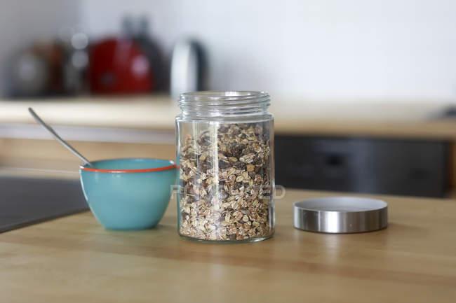 Glas Müsli und eine Schüssel auf einem Küchentisch — Stockfoto