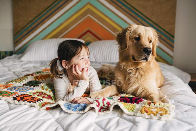 Jovem brincando com o cão em uma cama — Fotografia de Stock