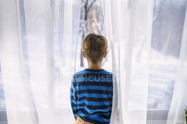 Boy looking out of a window — Stock Photo