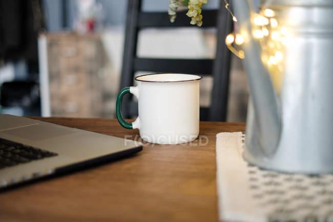 Крупный план кружки рядом с ноутбуком на столе — стоковое фото