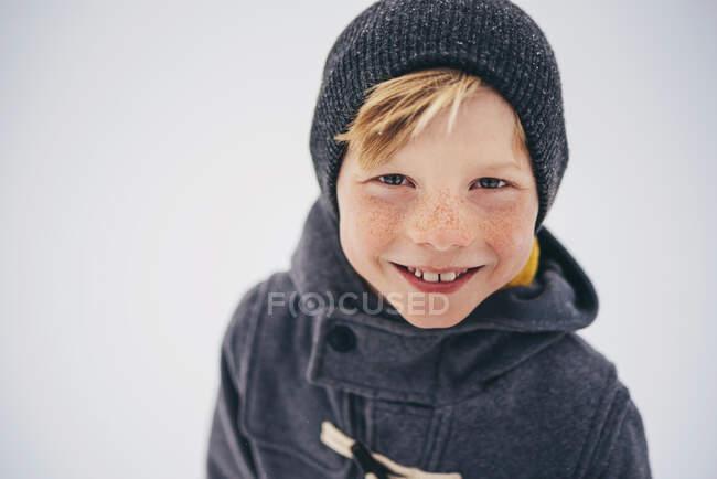 Retrato de un niño sonriente sosteniendo una corona de Navidad - foto de stock