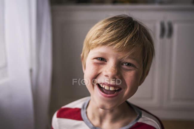 Retrato de un niño sonriente con pecas - foto de stock