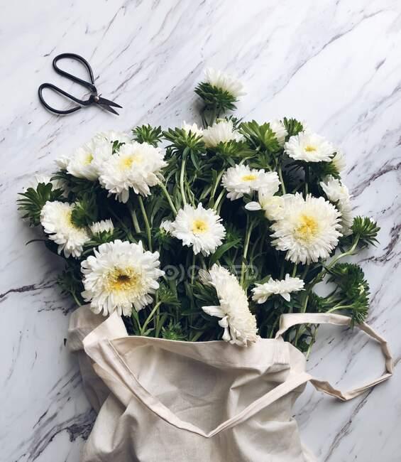 Bouquet di fiori bianchi in una borsa di lino — Foto stock