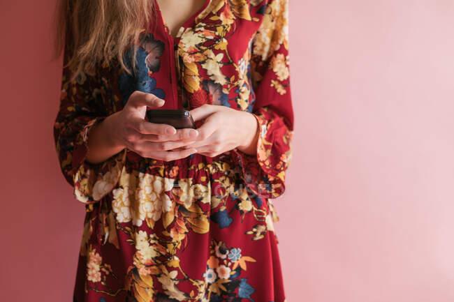 Mujer de pie contra una pared usando un teléfono móvil - foto de stock