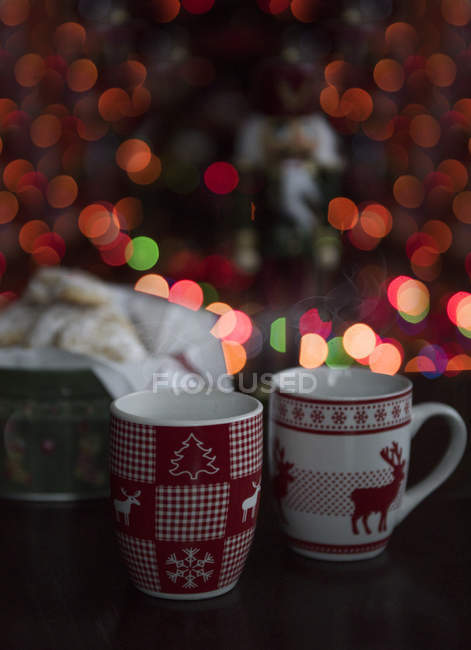 Two Christmas mugs in front of a Christmas tree — Stock Photo