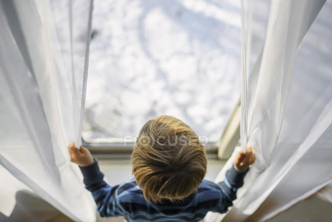 Мальчик смотрит из окна на снег — стоковое фото