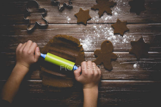 Boy making gingerbread cookies, rolling out cookie dough — Stock Photo