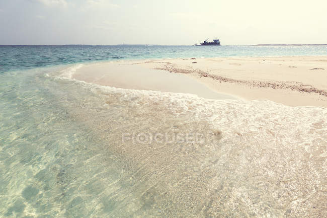 Scenic view of Tropical beach with a ship in distance, Maldives — Stock Photo