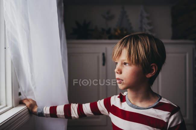 Мальчик смотрит из окна на дом — стоковое фото