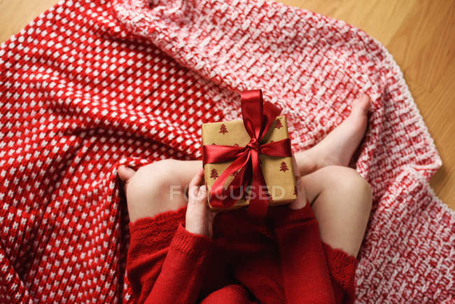 Overhead view of a girl sitting cross-legged holding a wrapped Christmas gift — Stock Photo