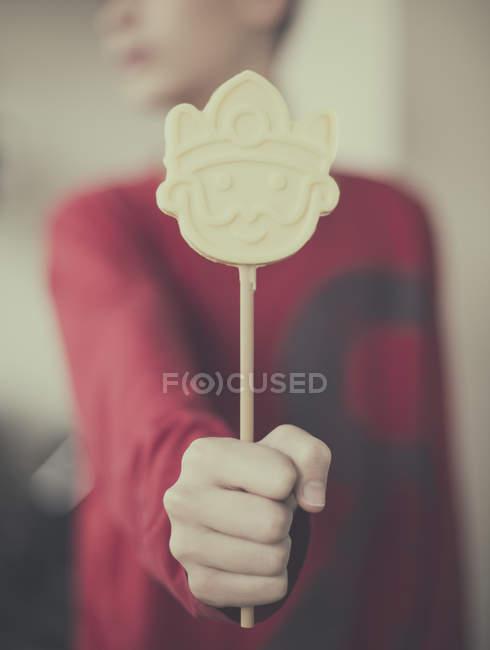 Menino segurando pirulito de chocolate branco — Fotografia de Stock