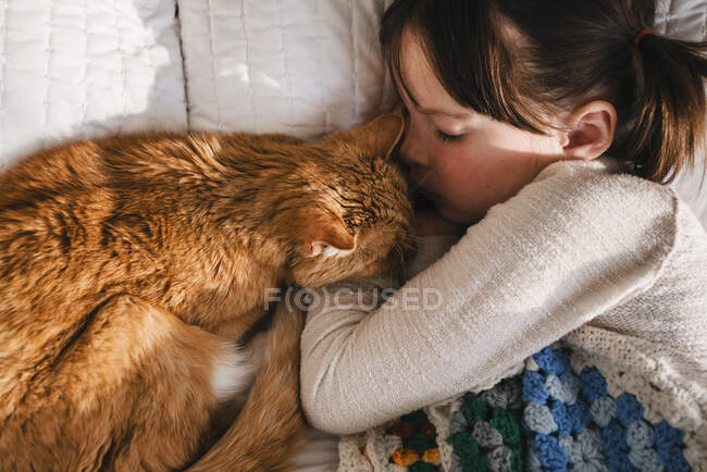 Young girl sleeping on bed with cat — Stock Photo