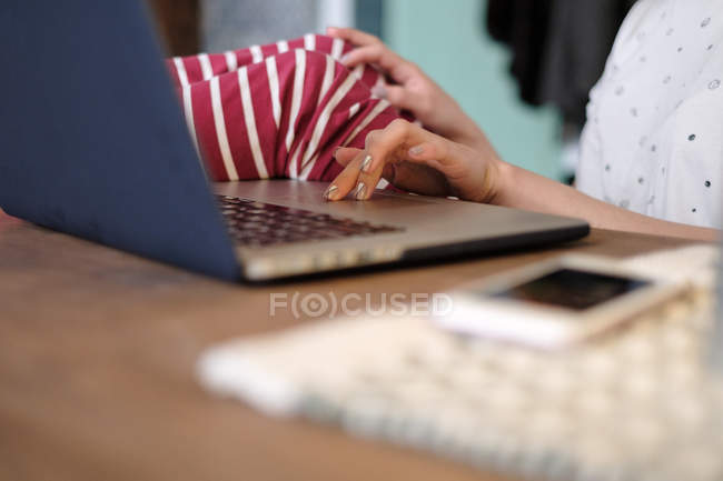 Woman sitting at a table using her laptop computer, cropped — Stock Photo