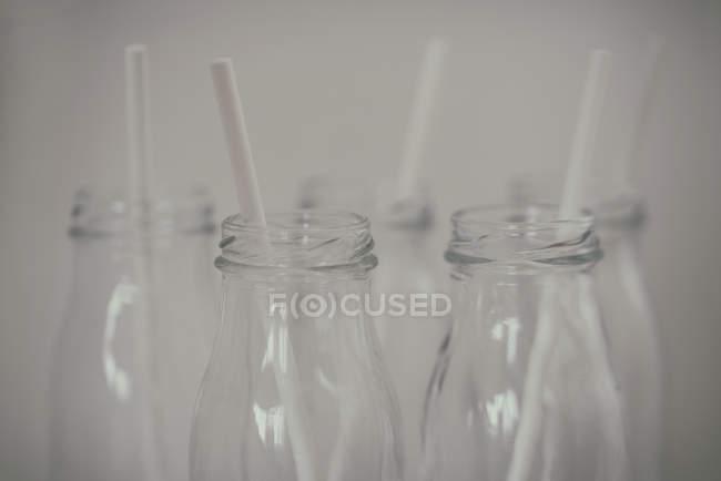 Primo piano vista di cinque bottiglie di vetro con cannucce da bere — Foto stock
