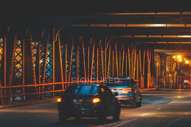Cars driving under elevated train tracks and bridge over Chicago river at night, Illinois, United States — Stock Photo