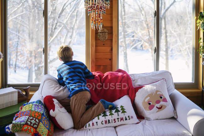 Вид сзади мальчика, выглядывающего из окна на рождественский снег — стоковое фото