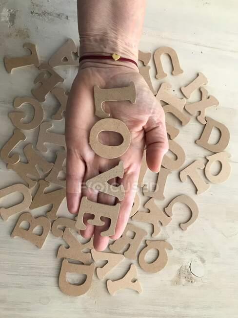 Жіноча рука тримає листи, в яких написано слово