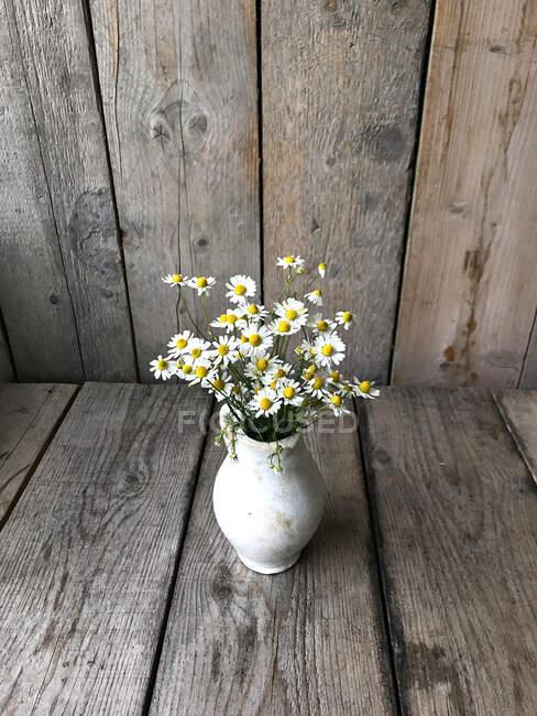 Ваза с маргаритками на деревянном столе — стоковое фото