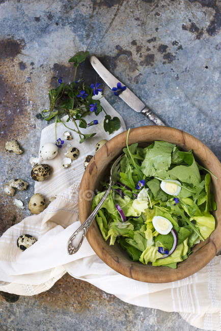 Salad with quail eggs and edible flowers — Stock Photo