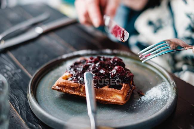Крупним планом вид жінка їсть вафлі з джемом — стокове фото