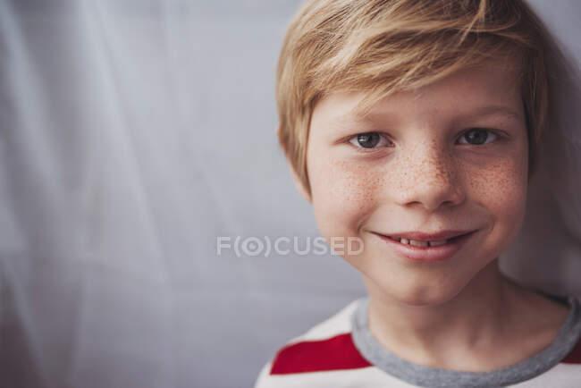 Портрет мальчика с веснушками, стоящего у занавеса — стоковое фото