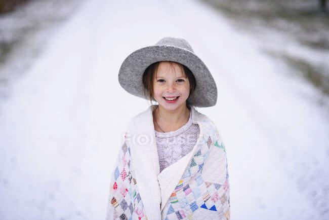 Giovane ragazza con cappello fuori avvolto in una trapunta — Foto stock