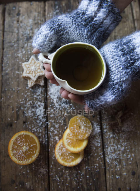 Женщина в бесформенных перчатках, держащая чашку травяного чая в форме сердца — стоковое фото