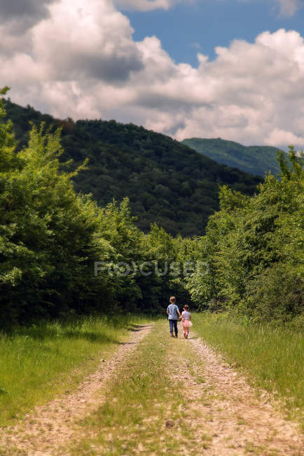 Junge und Mädchen gehen auf einem ländlichen Fußweg — Stockfoto